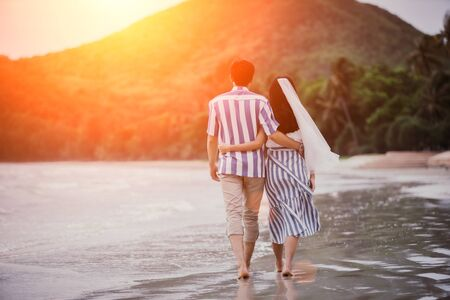 Couples young man and women are embracing each other to see the sea and sunset along the coastline. Romantic couple relaxing on the beach. Banque d'images