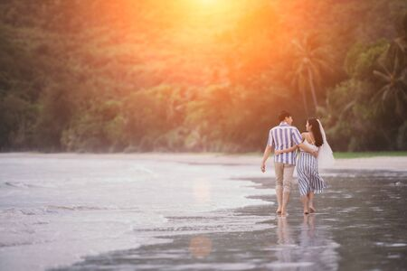 Happy romantic couples strolling and watching the beautiful sunset on the evening beach. Warm love on valentines day.