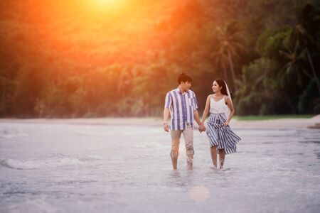Valentines Day, Couple held their hands and walked smoothly on the seashore watching the sunset happily. Men and women smile and look at each other with love.