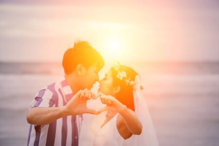 Valentine day, Young couple make heart-shaped hands with kissing in the background. Honeymoon lovers after marriage. Reklamní fotografie