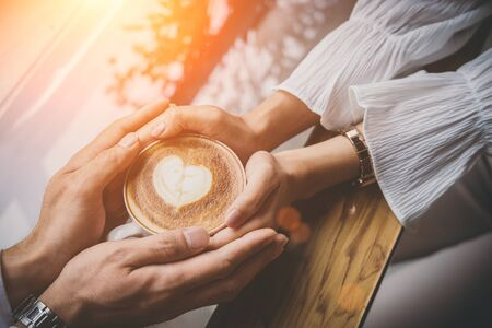 Valentine day, Close up of a young lovers hand holding a heart shaped coffee cup on a wooden table in the coffee shop. Warm Tone. Couple wedding. Stok Fotoğraf