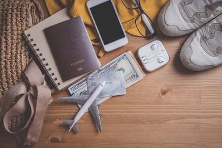 Travel concept - Top view model plane with passport, Yellow hat and smartphone and headphones and bag on a wooden table. Traveler accessories. Reklamní fotografie