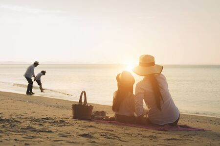 Holiday travel concept, Summer vacations. Happy family are having fun on a tropical beach. Mother and daughter sit happily watching father and son playing on the sea.