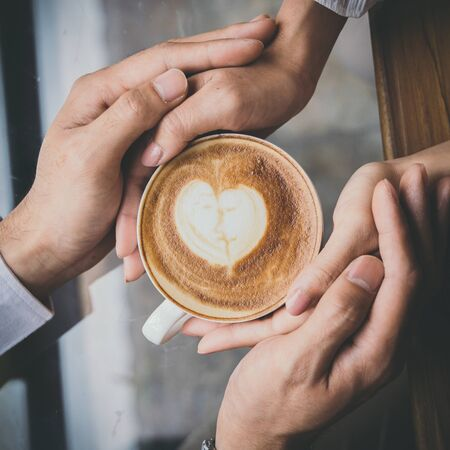 Valentine day, Top view of a young lovers hand holding a heart shaped coffee cup on a wooden table in the coffee shop. Warm Tone.