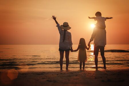Summer vacation, Happy family  together on the beach in holiday. Silhouette of the family holding hands enjoying the sunset on the tropical beach. Banque d'images