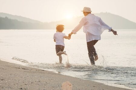 Happy family with little boy walking together on a tropical beach during the summer holidays. Happy father and son running on the beach in the morning. Reklamní fotografie