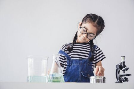 Scientist concept - Children's scientists tested under a microscope in a modern laboratory. Little girl is excited and fun with the experiment.