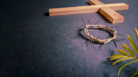 Lent Season,Holy Week and Good Friday concepts - image of wooden cross,crown of thorns and palm leave in vintage background