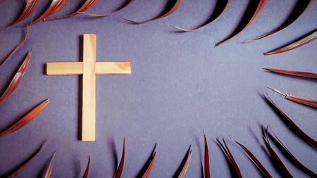 Lent Season,Holy Week and Good Friday concepts - photo of wooden cross with palm leave in vintage background