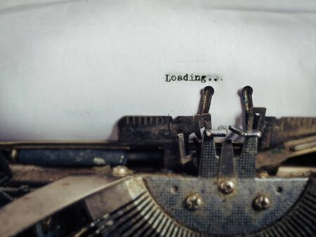 Loading text typed on white paper in vintage background. Stock photo. 版權商用圖片
