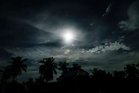 A full moon night in a village with clouds above and buildings and trees below with halo surrounding the moon Standard-Bild