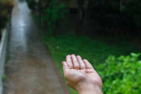 Isolated wet human hand with rain drops falling on it Standard-Bild