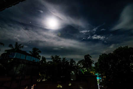A full moon night in a village with clouds above and buildings and trees below with lights peeping through the trees Standard-Bild