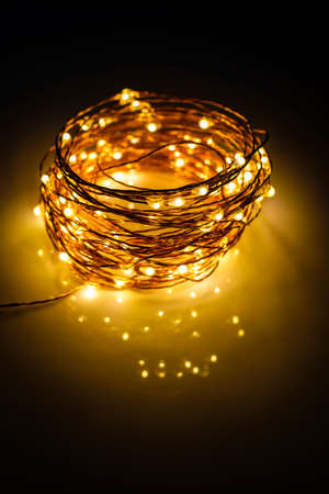 Yellow colored light chain for decoration placed on a reflective surface. Portrait view