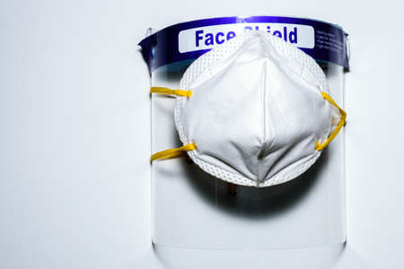 A face mask covered on a face shield placed on a white surface. To use for personal protection against covid 19
