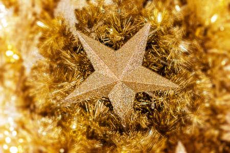 Sluit omhoog van gouden Kerstmisster op gouden Kerstboom