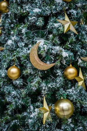 Sluit omhoog van gouden Kerstmismaan, ster en bal op Kerstboom