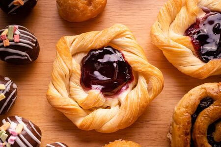 danish pastry toppings with blueberry jam and many kind of bakery on wooden background Stockfoto