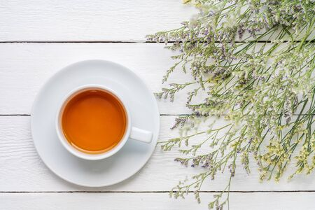 A cup of tea on white painted wood background with branch of small flower
