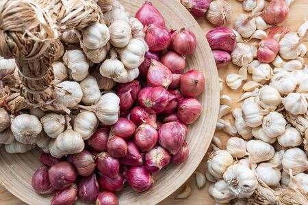 Garlic and shallot or red onion in a wooden dish