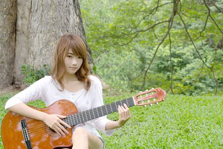 nylon string: Thai cute girl with nylon string guitar in the garden 2