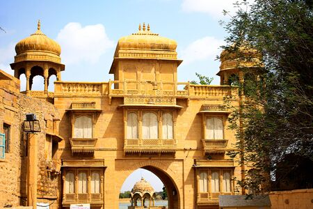 historical gateway building in yellow sandstone on lake shore