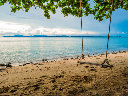 Wooden swing on the Beach beside the ocean in vacation time,summer concept