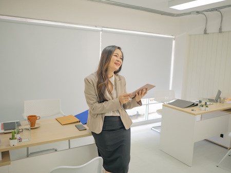Modern business women in the office and use Tablet while Smile like very happy,business concept 版權商用圖片