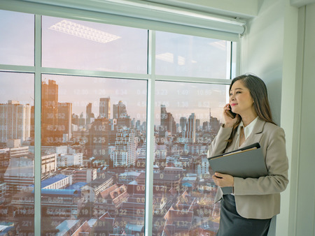 Modern business women use mobilephone talk about stock market white looking out of the window,cityscape with stock number,business concept Foto de archivo