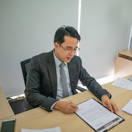 Happy asian business man look at his document file in the office,business concept