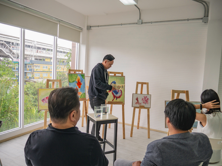 Handsome Young Asian man or water color artist Teaching how to paint in studio,fish concept