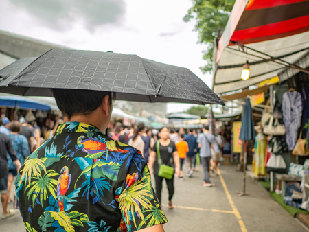 Handsome Asian male wear hawai t -shirt Holding umbrella and walking in the Chatuchak park Bangkok thailand