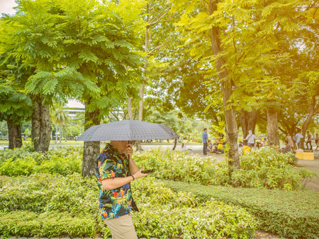 Handsome Asian male wear hawai t -shirt Holding umbrella and walking in the park Bangkok thailand Banque d'images - 118563007