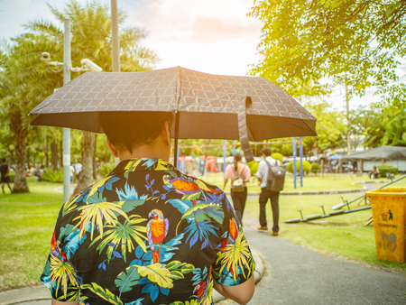 Handsome Asian male wear hawai t -shirt Holding umbrella and walking in the park Bangkok thailand