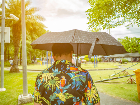Handsome Asian male wear hawai t -shirt Holding umbrella and walking in the Chatuchak park Bangkok thailand Banque d'images - 118616111