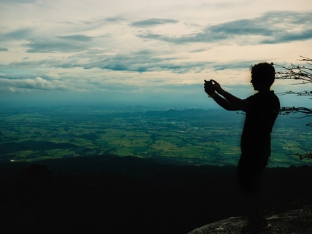 Silhouette Photo of Tourist stand on the cliff and Takeing the photo on Khao Luang mountain in Ramkhamhaeng National Park,Sukhothai province Thailand Imagens