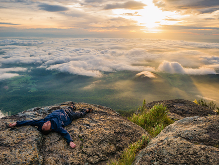 Trekker Lay down on the cliff with Beautiful Sunrise and sea of mist in the morning on Khao Luang mountain in Ramkhamhaeng National Park,Sukhothai province Thailand