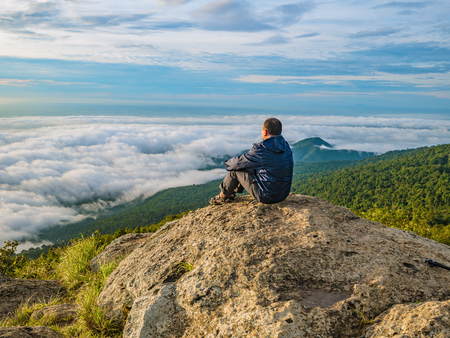 Asian men Sit on the cliff with beautiful  sky on Khao Luang mountain in Ramkhamhaeng National Park,Sukhothai province Thailand Stockfoto