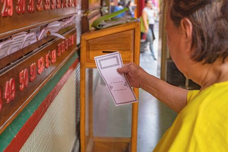 Senior Asian women Pick up Chinese daily fortune teller paper in  Wat Mangkon Kamalawat temple in bangkok thailand Stock fotó
