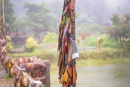Prayer tags tied to a pole on the bridge in the Pilok mine village in kanchanaburi City Thailand.Pilok mine The Old mine near the Thai-Myanmar border