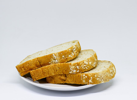 the slice Whole wheat  bread on the white disc on the isolate background  it look very delicious and good for health 版權商用圖片