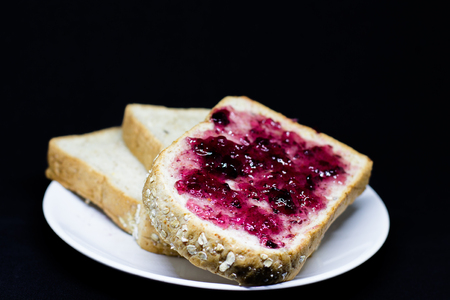 strawberry jam sandwich: bread with spread grapejam on the  white dish on black  isolate background