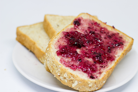 strawberry jam sandwich: bread with spread grapejam on the  white dish on white  isolate background Stock Photo