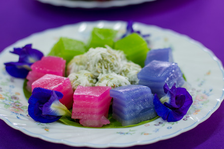 traditional thai desserts , Colorful of Thai steamed layer cake in cube and rose shape,call Khanom Chan in Thai copy space on the purple table