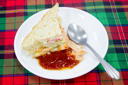 sandwitch: vegetables sandwiches serve with fried potato good food and healthy for diet and control weight with the tomatoes sauce on the white disc and the Stainless spoon on the Scottish chintz