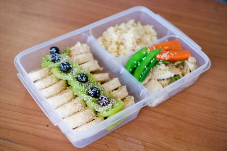 bread salad roll wrap sandwich with berry, lettuce,  kiwi ,bananas and bean , chicken breast with rice on the rice box