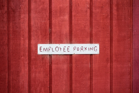 Employee Parking Sign on Red Wooden Wall