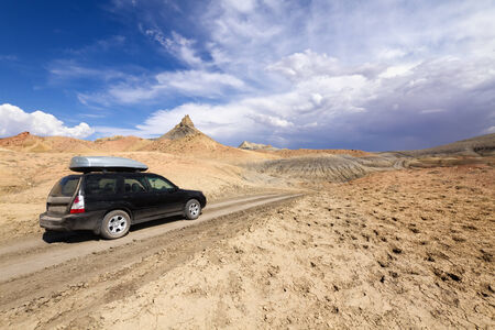 SUV driving on desert dirt road to Lake Powell under stormy sky, Glen Canyon National Recreation Area Stock Photo