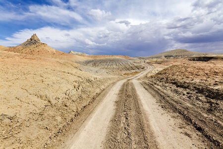 Desert dirt road to Lake Powell under stormy sky, Glen Canyon National Recreation Area