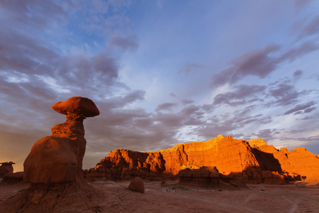 goblin: Sandstone rock hoodoos glowing at sunset under stormy sky Goblin Valley State Park UT. Stock Photo